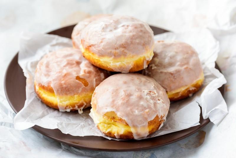 Polskie pączki zamiast posypywać cukrem pudrem ,częściej polewa się lukrem, również z dodatkiem skórki pomarańczowej.